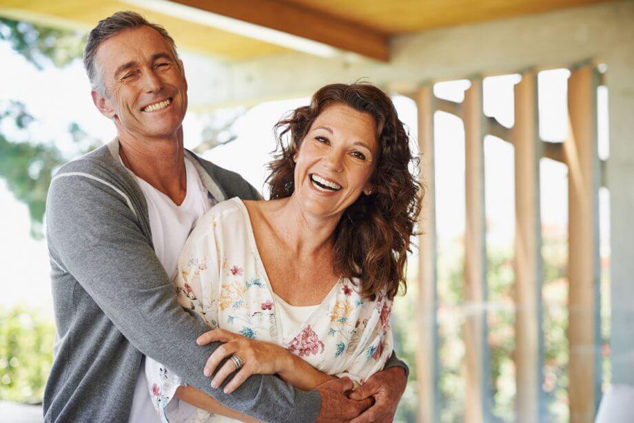 older smiling couple hugging on porch
