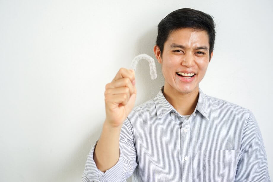 Man wearing a button down shirt, smiling and holding an Invisalign aligner.