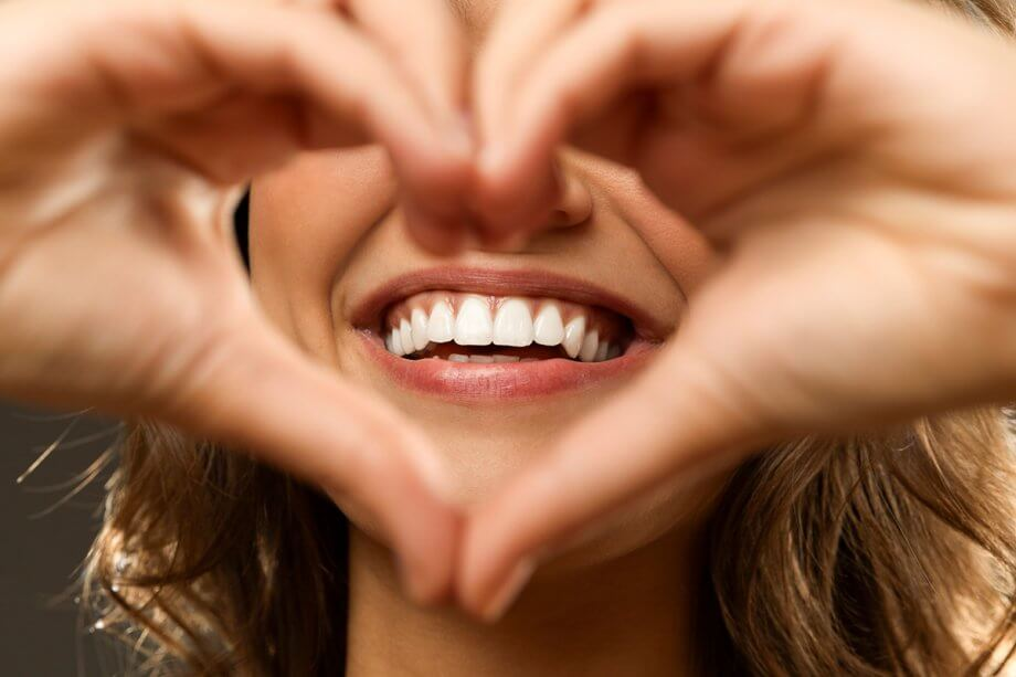 woman making heart shape with hands around smile