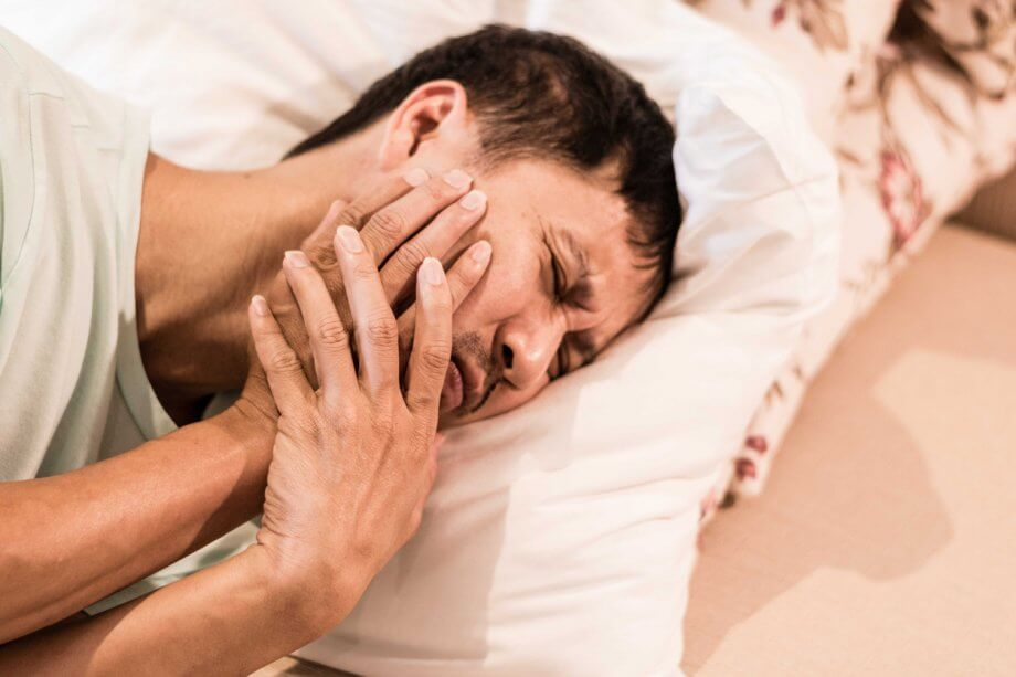 Man Lying in Bed with TMJ Symptoms