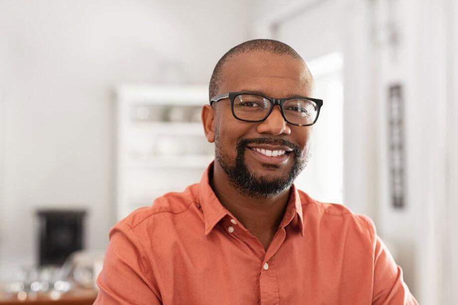 smiling man in orange Oxford shirt