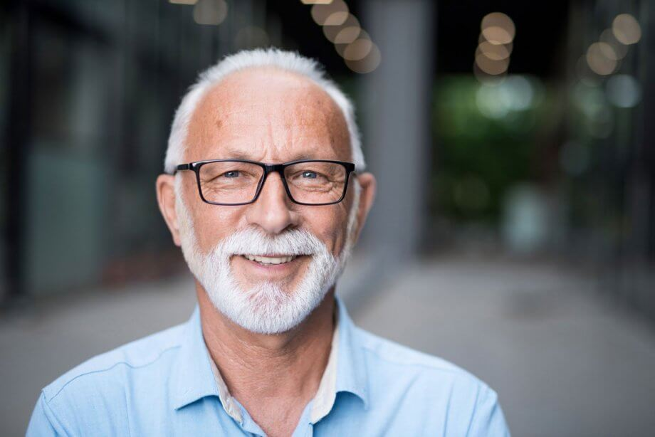 older man with beard and black-rimmed glasses