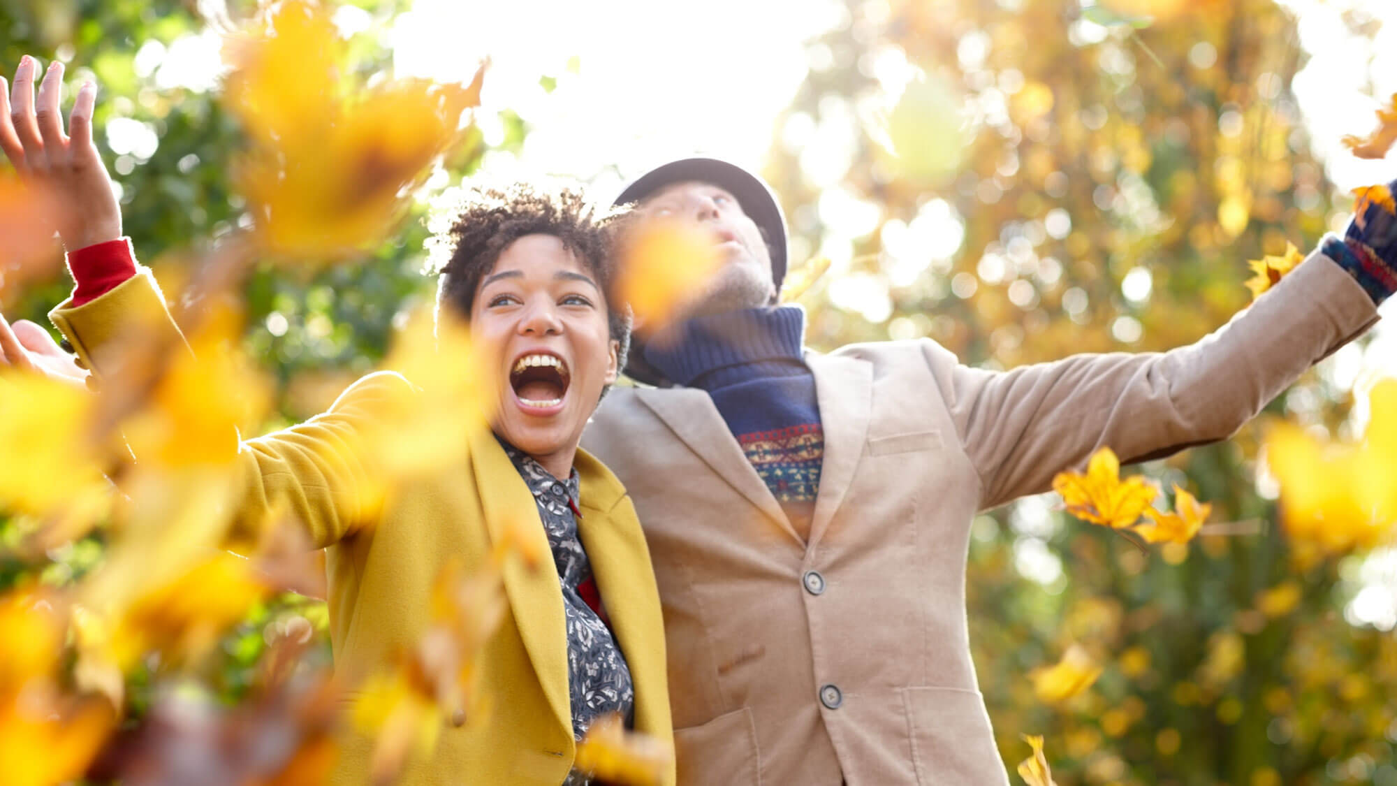 a couple outside in the fall having fun throwing leaves in the air