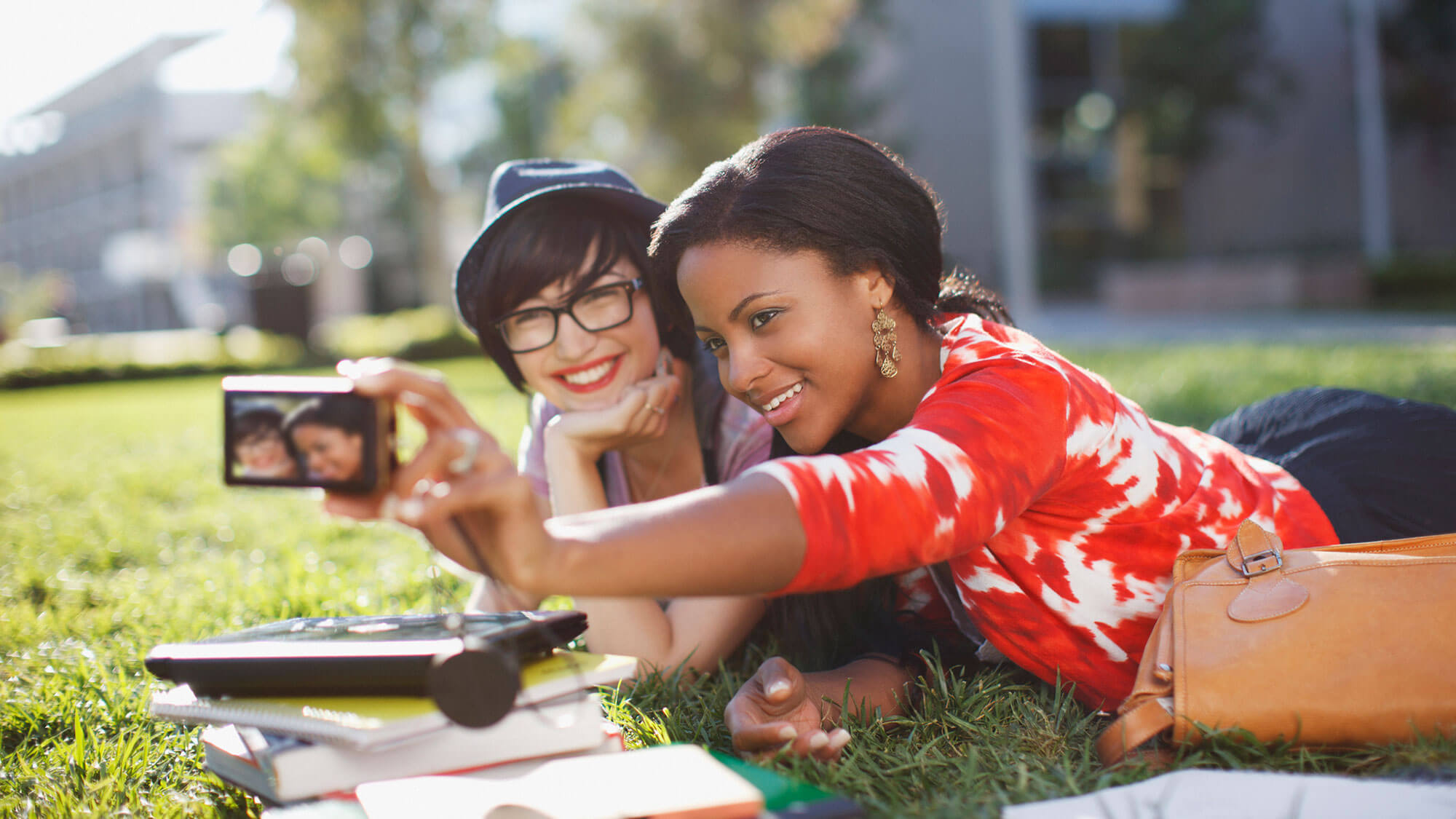 two young girls outside on the grass taking a selfie