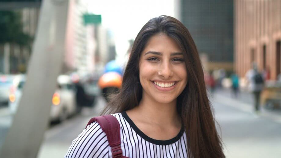 young smiling woman standing on city sidewalk